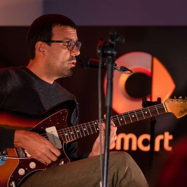 Miguel Araújo sentado numa cadeira a cantar e a tocar guitarra no palco do concessionário smart