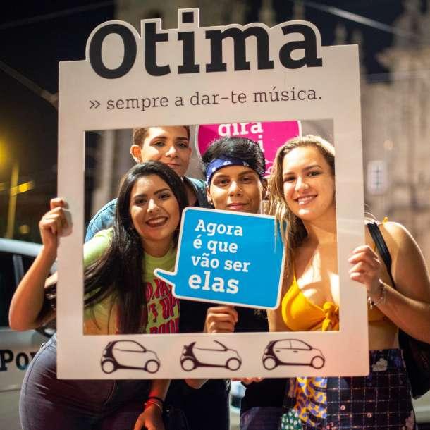 Pessoas a tirar uma fotografia com elementos gráficos de promoção à Otima Smart Porto
